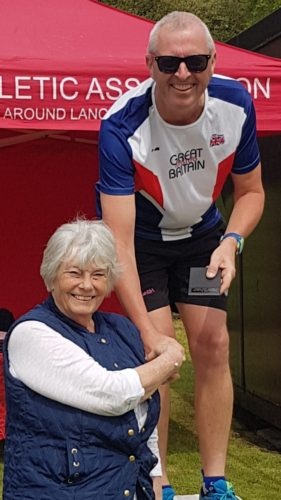Mark Crompton receives his mgold medal from Margaret Crompton
